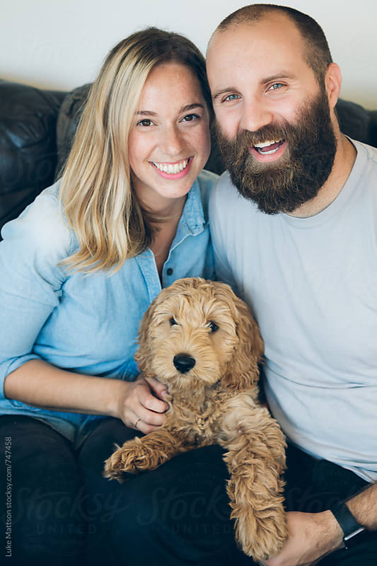 Happy Young Couple Sitting On Couch With Pet Labradoodle Puppy by Luke Mattson for Stocksy United