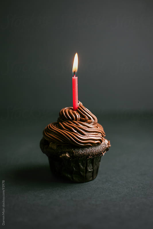Cupcake with candle.  by Darren Muir for Stocksy United