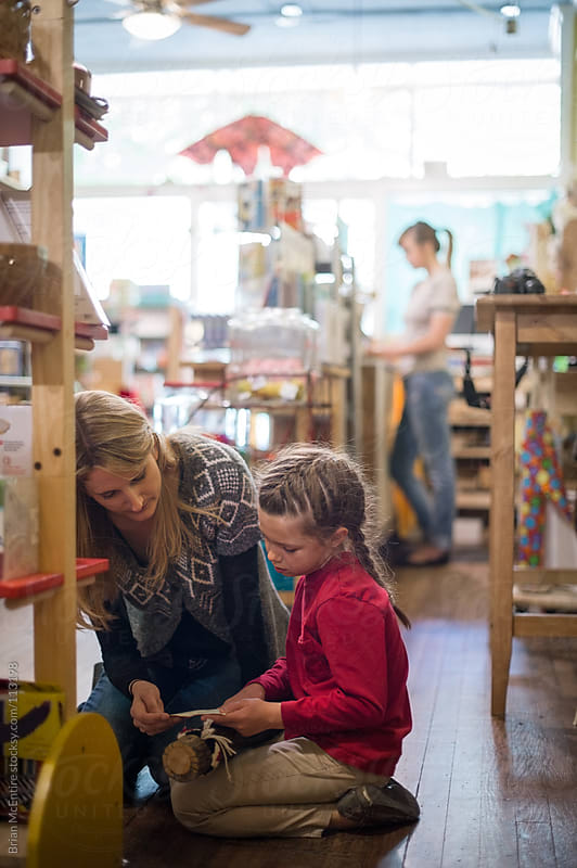 Mother and Daughter Reading in Toy Store by Brian McEntire for Stocksy United