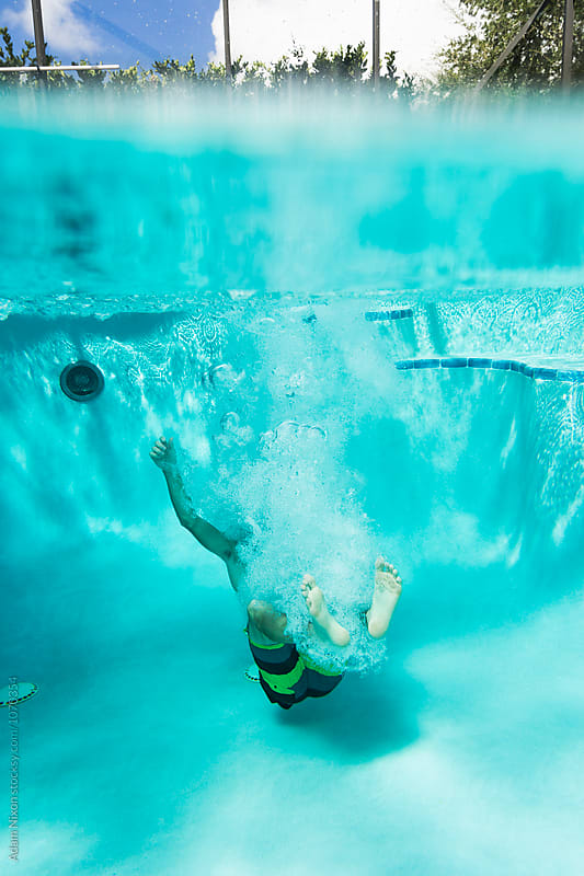 Teenager jumping into a swimming pool by Adam Nixon for Stocksy United