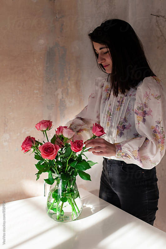 Beautiful woman arranging a bouquet of roses indoor by VeaVea for Stocksy United