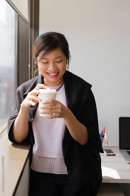 Businesswoman holding a cup of coffee by Alita Ong for Stocksy United