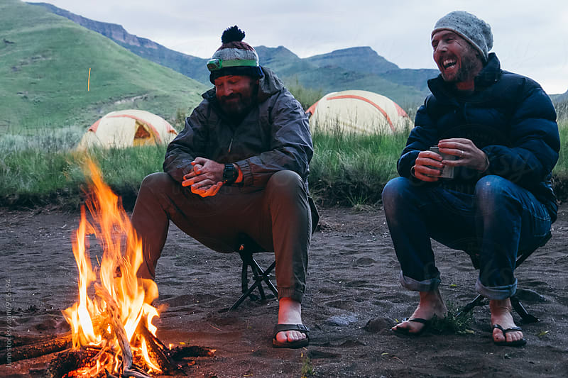 hikers around a camp fire in the mountains at dusk by Micky Wiswedel for Stocksy United