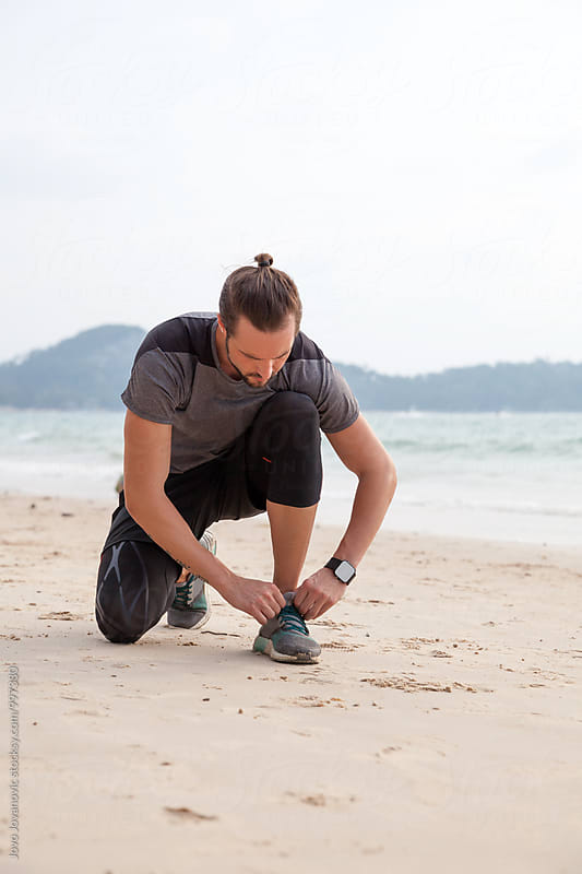 Man tying sports shoe at beach before workout by Jovo Jovanovic for Stocksy United