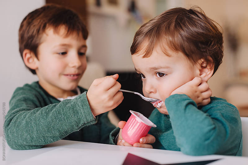 Young boy helping his little brother to eat a strawberry yoghurt. by BONNINSTUDIO for Stocksy United