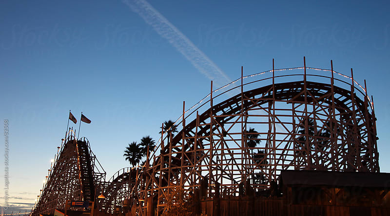 Night time scene at the Boardwalk of the roller coaster by Carolyn Lagattuta for Stocksy United