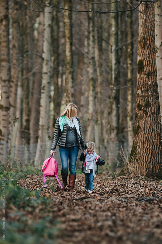 cute little girl and her pregnant mother walking through foliage covered forest carrying a pink schoolbag by Leander Nardin for Stocksy United