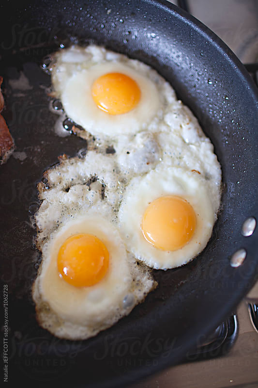Cooking fried eggs and bacon at home for breakfast by Natalie JEFFCOTT for Stocksy United