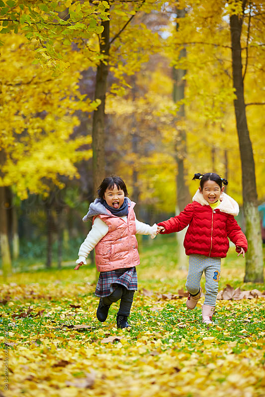 two asian little girl having fun in the autumn woods by Bo Bo for Stocksy United