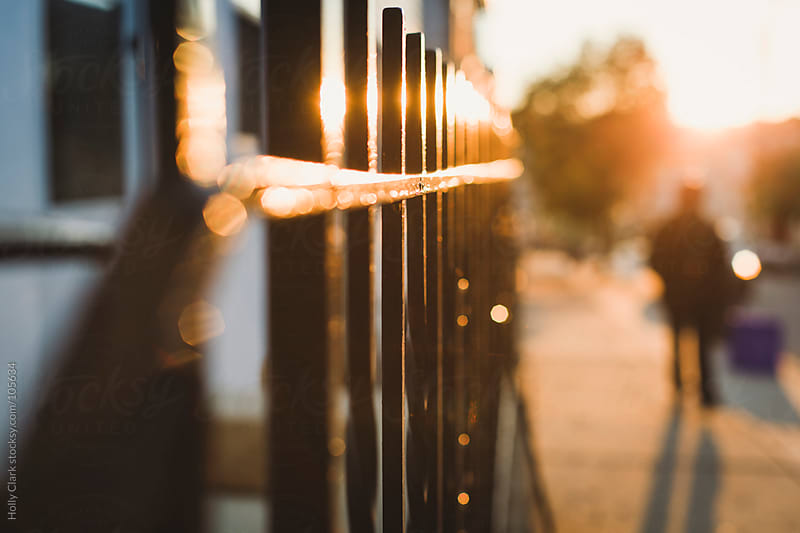 The setting sun shines on a city fence as a person walks down th by Holly Clark for Stocksy United