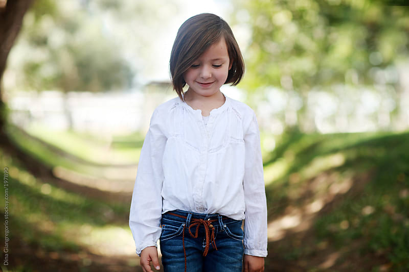 Little girl wearing white standing among trees looking innocent by Dina Giangregorio for Stocksy United