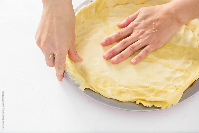 Young woman's hands putting dough for baking pie by Lawren Lu for Stocksy United