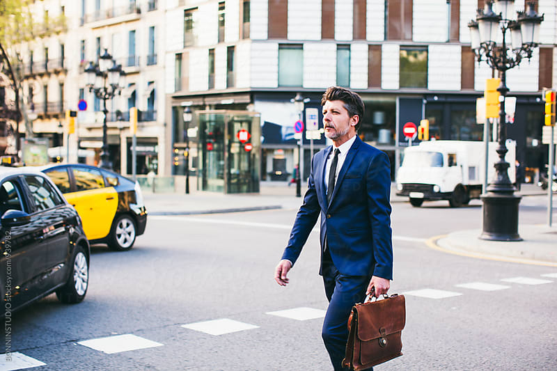 Mature businessman holding the briefcase crossing the street. by BONNINSTUDIO for Stocksy United