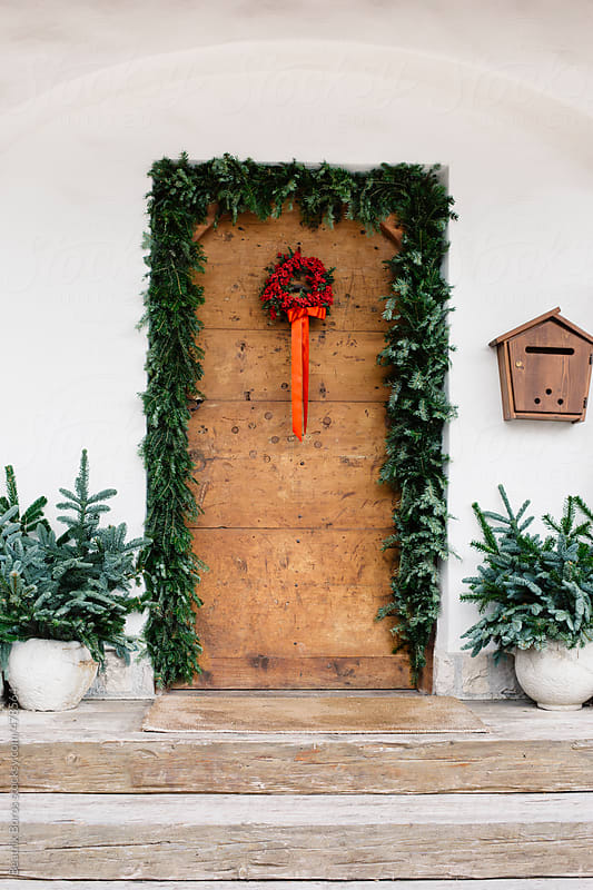 Rustic, wooden front door naturally decorated for Christmas with pine branches and a berry wreath  by Beatrix Boros for Stocksy United