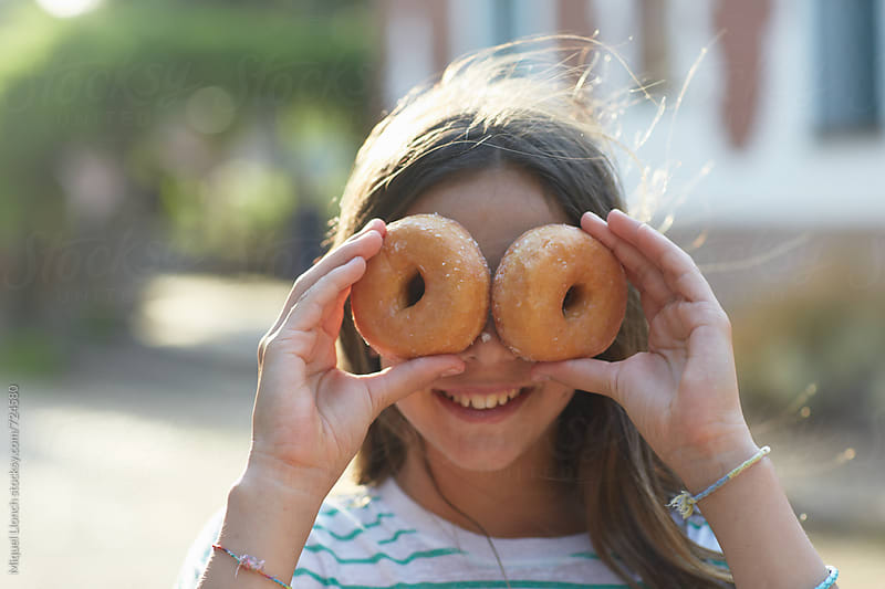 Young girl with two doughnuts covering her face and looking at camera by Miquel Llonch for Stocksy United