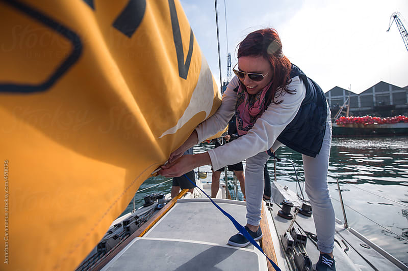 Young woman rigging sail on deck of yacht sailboat in the harbour by Jonathan Caramanus for Stocksy United