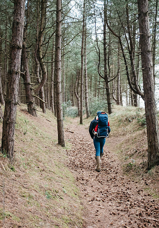 Young father walking in woodland with his daughter in a baby carrier backpack. Norfolk, UK. by Liam Grant for Stocksy United