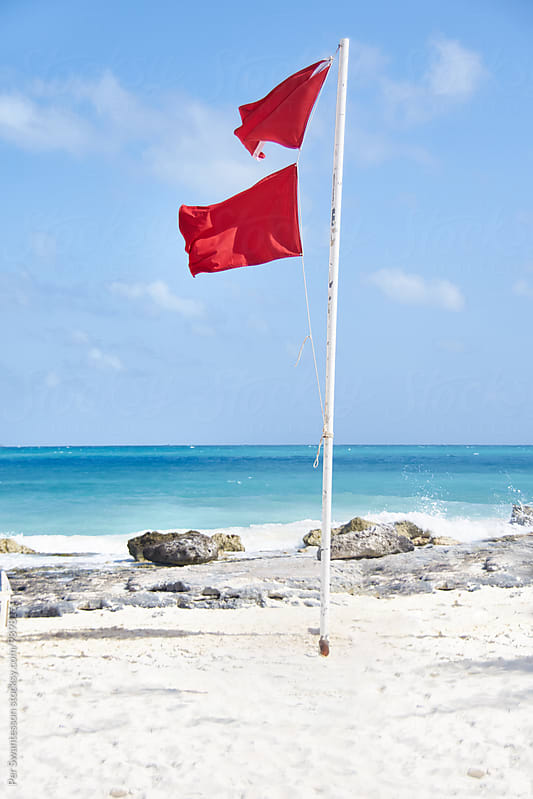 Tropical beach with red warning flag by Per Swantesson for Stocksy United