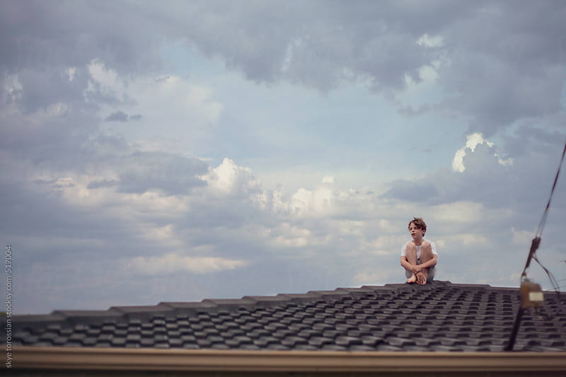 Boy on a roof top. by skye torossian for Stocksy United