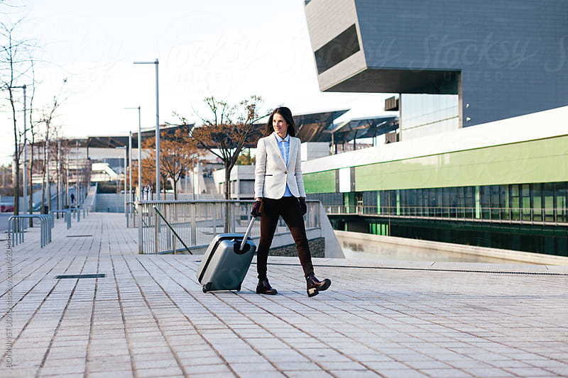 Young businesswoman rolling luggage to the airport.  by BONNINSTUDIO for Stocksy United