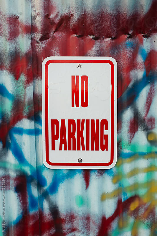 No Parking sign on graffiti covered wall by Paul Edmondson for Stocksy United