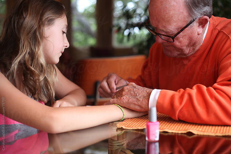 Grandfather filing and painting his granddaughter's fingernails by Carolyn Lagattuta for Stocksy United