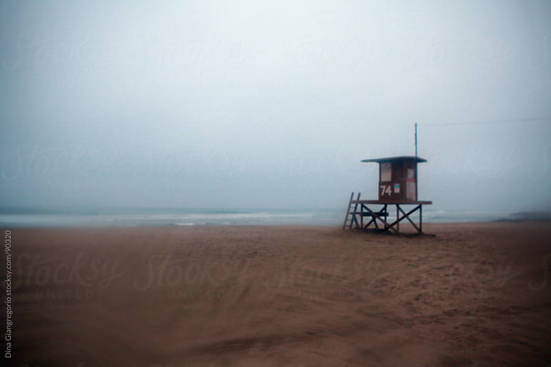 Dreamy view of a lifeguard tower on empty foggy beach by Dina Giangregorio for Stocksy United
