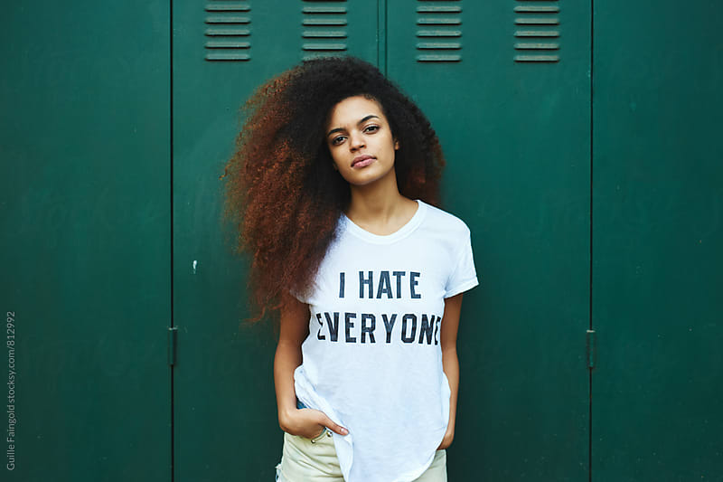 Beautiful young woman standing against of green lockers  by Guille Faingold for Stocksy United