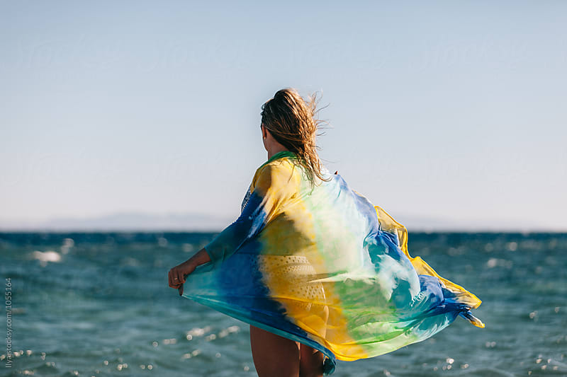 Young anonymous woman in bikini holding colorful cloth on tropical beach by Ilya for Stocksy United