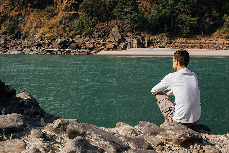 Man Sitting by the Ganges River by Mosuno for Stocksy United