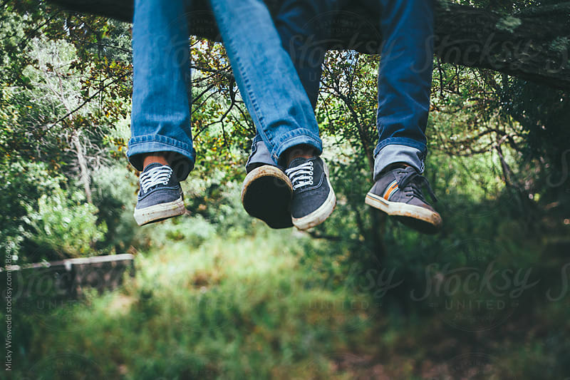 Feet of a couple intertwined whilst sitting on a tree branch by Micky Wiswedel for Stocksy United