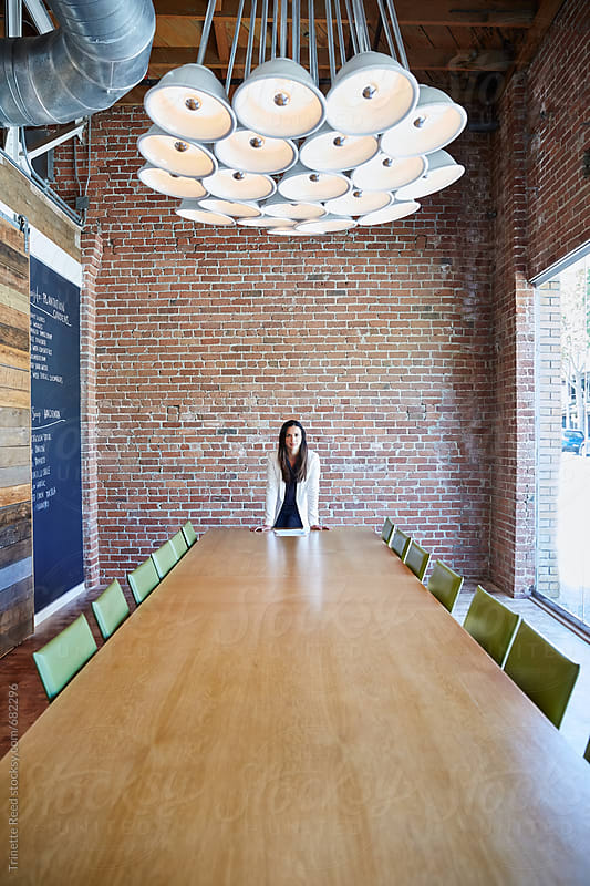 Portrait of millennial hispanic businesswoman in boardroom by Trinette Reed for Stocksy United
