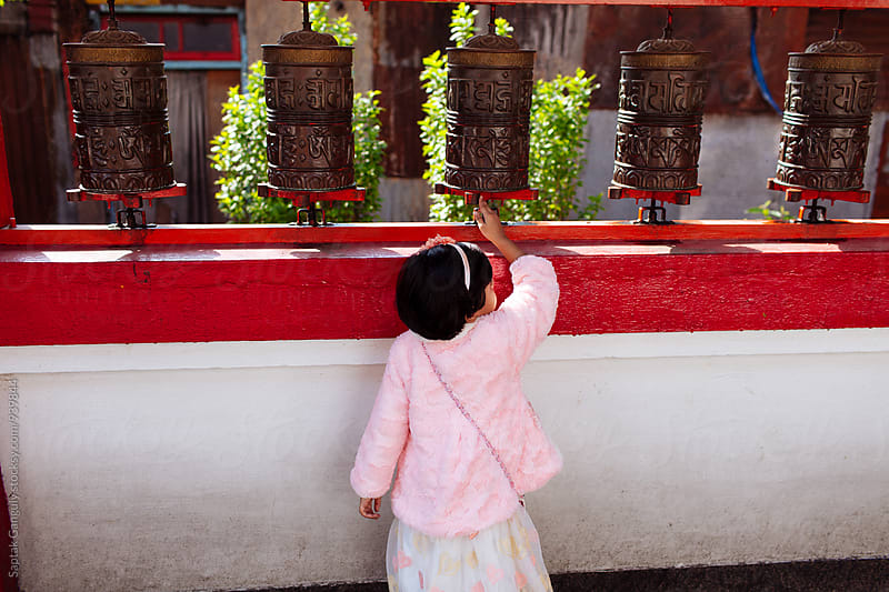 Little girl turning buddhist prayer wheels at a monastery by Saptak Ganguly for Stocksy United