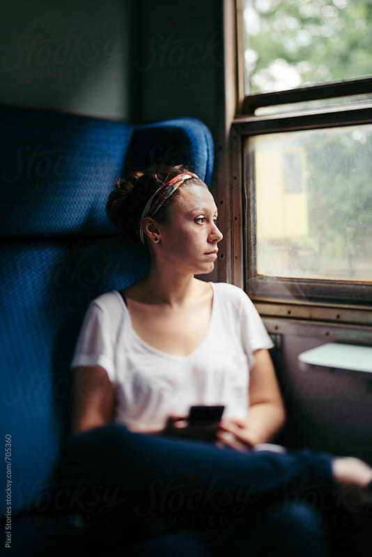 Pensive young woman looking through window by Pixel Stories for Stocksy United