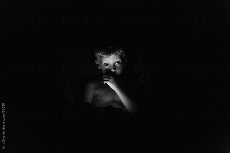 Boy with iPad in the Dark by Amy Drucker for Stocksy United
