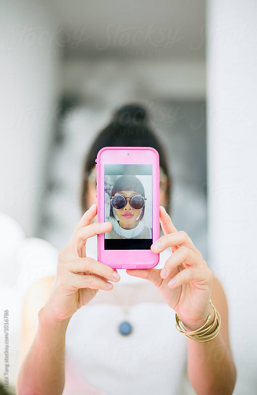 Young woman making self portrait with smartphone by Nabi Tang for Stocksy United