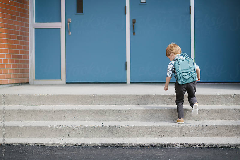 A blonde boy with a backpack running up the stairs of a school on his first day of school by Ania Boniecka for Stocksy United