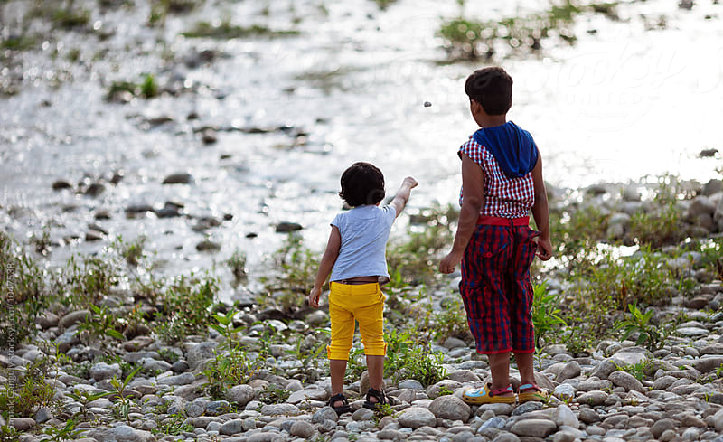 Brother and sister throwing stones at the river by Saptak Ganguly for Stocksy United