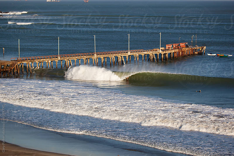 Perfect left breaking wave with a pier in the background in Peru by Gary Parker for Stocksy United