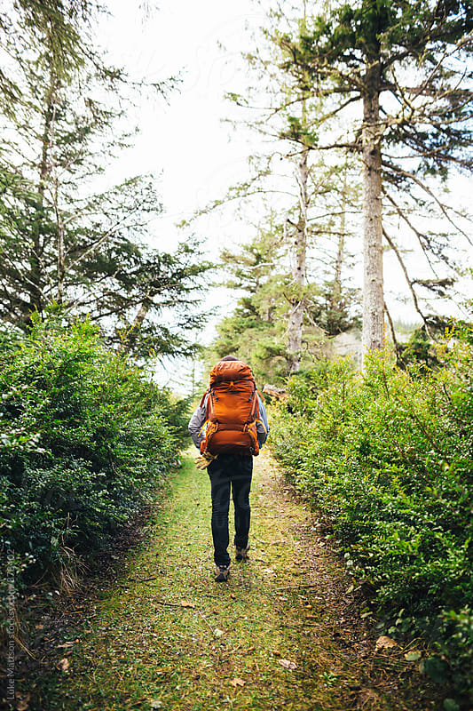 Man Wearing Large Orange Backpacking Backpack Hiking Along Grassy Forest Path by Luke Mattson for Stocksy United