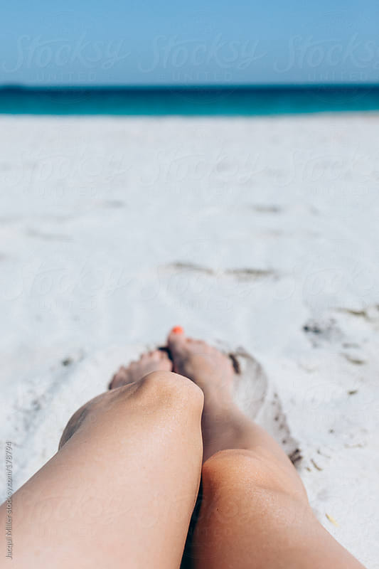 View of womans legs as she relaxes on the beach by Jacqui Miller for Stocksy United