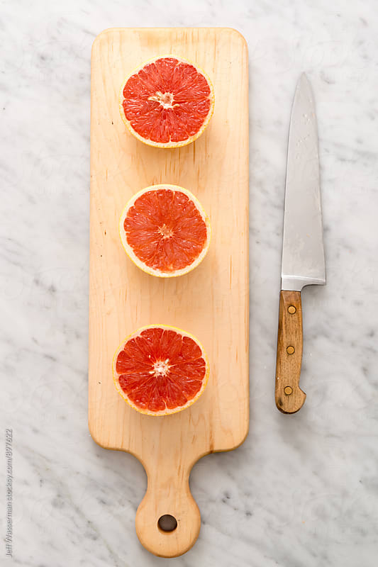 Grapfruit Halves on Cutting Board by Jeff Wasserman for Stocksy United