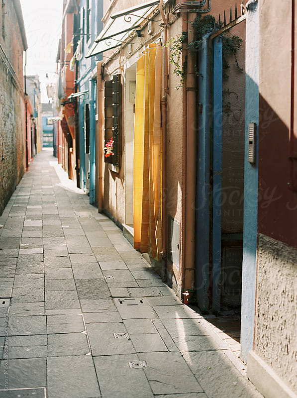 Looking down a colourful street in Burano, Venice by Kirstin Mckee for Stocksy United
