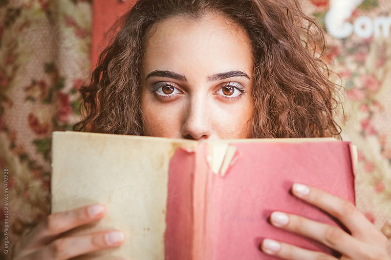 Beautiful Young Woman Holding an Old Book in front of her Face by Giorgio Magini for Stocksy United