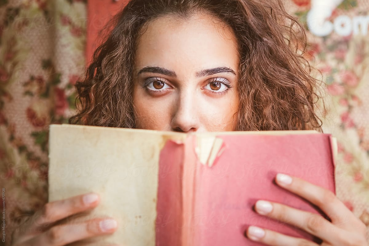Stock Photo Beautiful Young Woman Holding An Old Book In Front Of Her Face