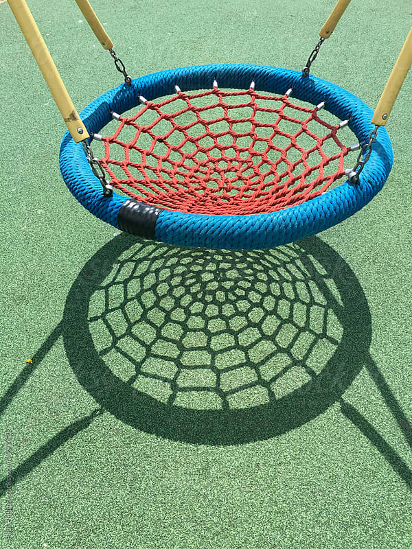 Children playground. Swing with strong shadow on safety  flooring. by Paul Phillips for Stocksy United
