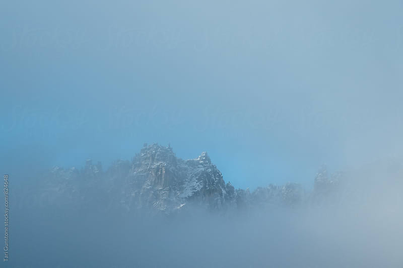 Snowy peak through fog by Tari Gunstone for Stocksy United