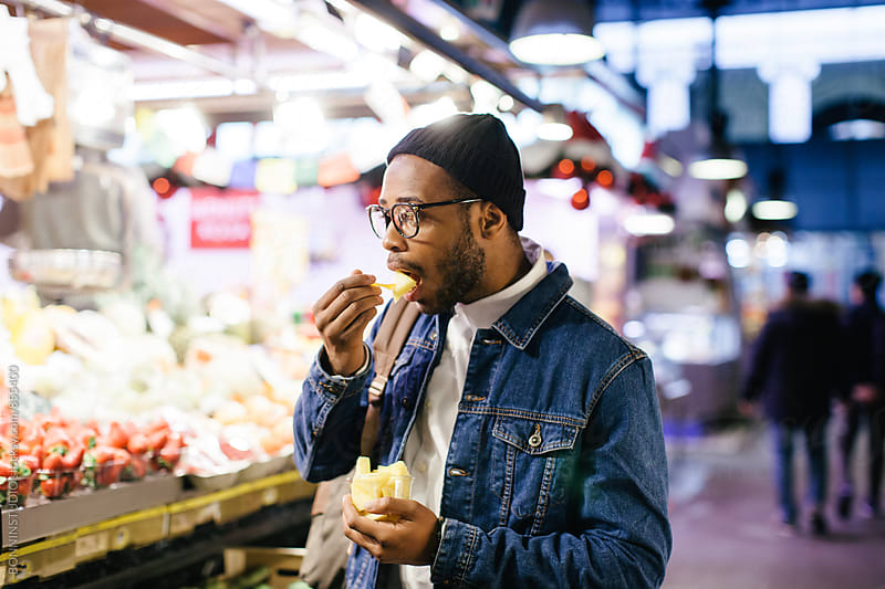 African american man eating pineapple in a marketplace. by BONNINSTUDIO for Stocksy United