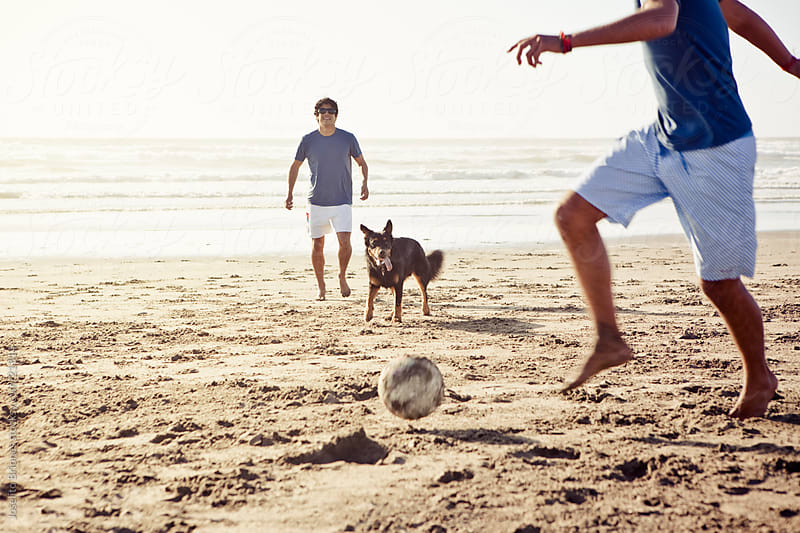 Latino Men Playing Beach Football with Pet Dog by Joselito Briones for Stocksy United