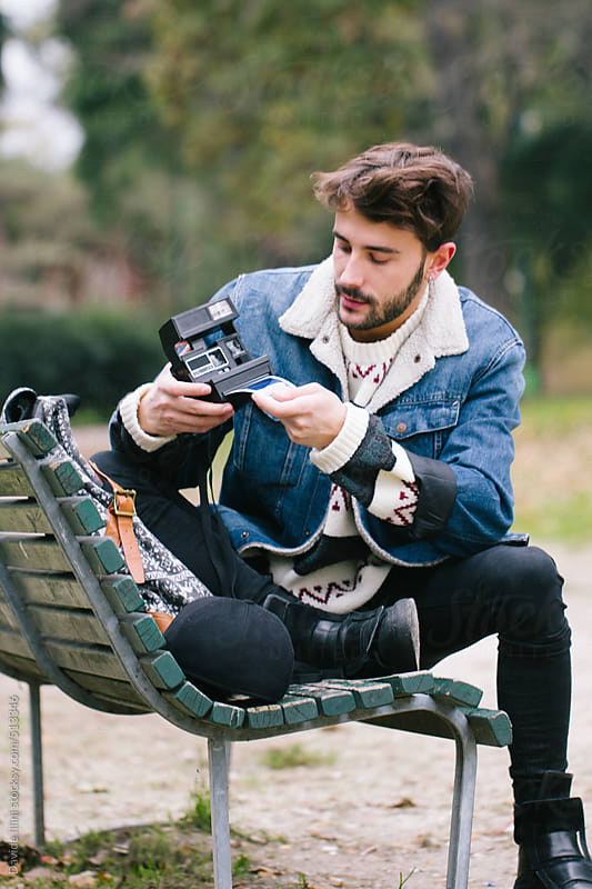 Young man takes pictures at the park with a instant camera by Davide Illini for Stocksy United